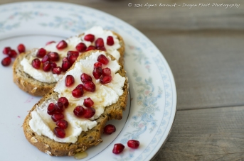 Goat cheese and pomegranate seeds with maple syrup on spelt rye and flax seed bread.