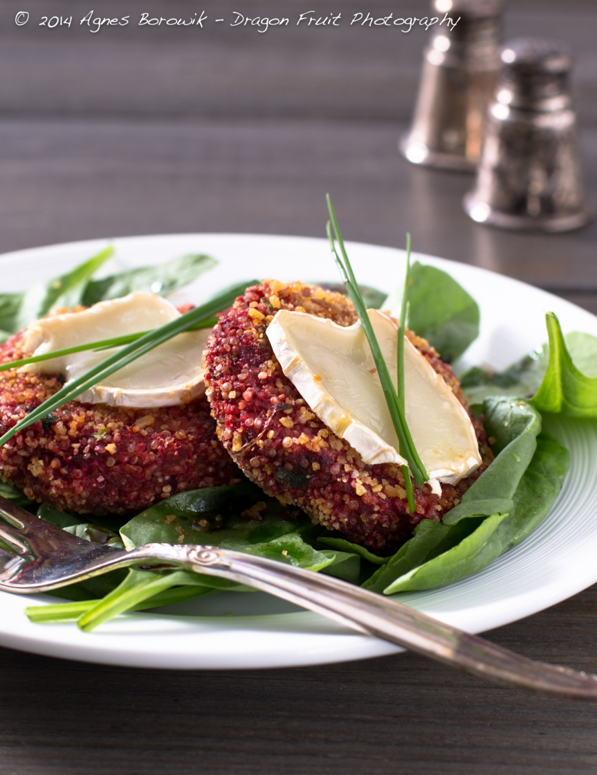 Quinoa and veggie burgers with goat cheese on a bed of baby spinach.